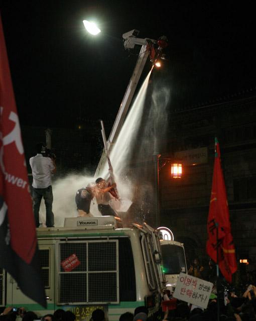 총학 깃발을 든 사람이 살수차의 직격을 맞고 있다.