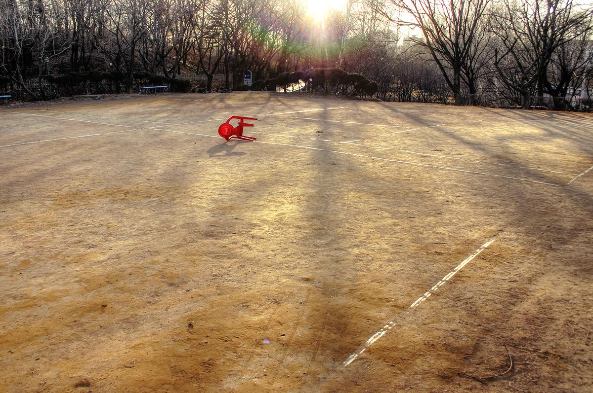 테니스코트에 넘어져있는 빨간의자-뒤로는 겨울나무들이 서 있고 그 사이로 노을이 떨어지고 있으며 테니스코트에는 겨울나무 그림자가 짙게 드리워있다.